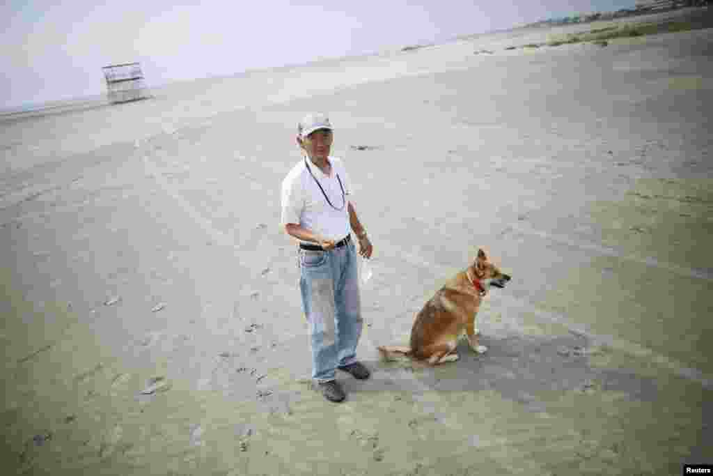 Local resident Takeshi Takaki, 71, and his dog stroll on the beach about 40 kilometers (25 miles) south of the nuclear power plant. The city of Iwaki closed its beach to the public during the summer season for the first time since the March 2011 earthquake that damaged the nuclear plant.