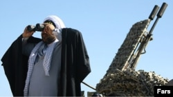 رجل دين إيراني يستخدم ناظوراً وخلفه مدفعية مقاومة للطائرات