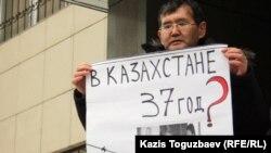 Almaty şäheriniň ýerli sudunyň oňünde oppozision aktiwistleriň tussag edilmegine protest bildirilip gurnalan pikete gatnaşyjylardan biri şygar göterip dur. Almaty, 26-njy ýanwar 2012.