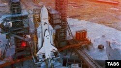A space shuttle orbiter using an Energia rocket as a launch vehicle sits on the launch pad in the 1980s.