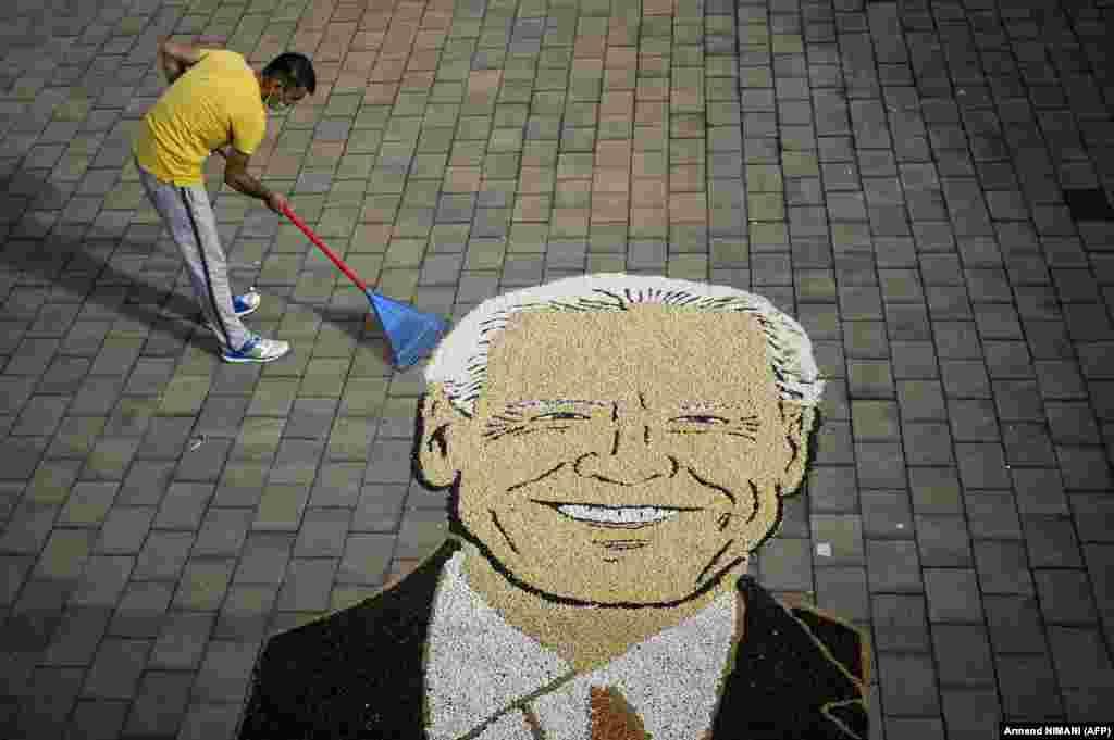 Kosovar artist Alkent Pozhegu works on the final touches of an image made with grain and seed, depicting Joe Biden, the U.S. Democratic presidential nominee, in the town of Gjakova. (AFP/Armend Nimani)​