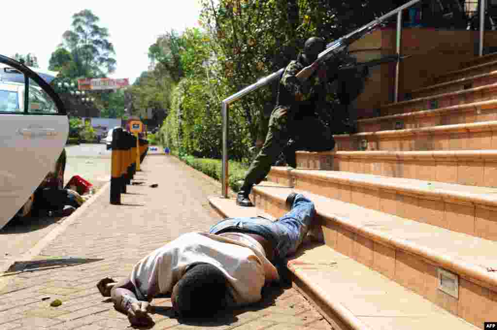 A man lies on the ground as armed policemen try to enter the shopping center after the initial attack on September 21.