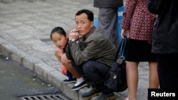 Луѓе чекаат на автобуска станица, Пјонгјанг, 17.04.2017.