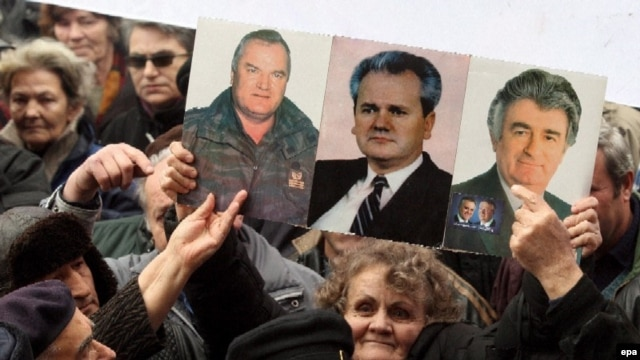 Nationalists hold up pictures of Ratko Mladic, Radovan Karadzic, and Slobodan Milosevic at a rally in 2007. Now they are rallying for Libya's Muammar Qaddafi.