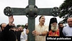 М. Саакашвили Баграти чиркөөсүнүн крестин кармап турат. Кутаиси шаары.
