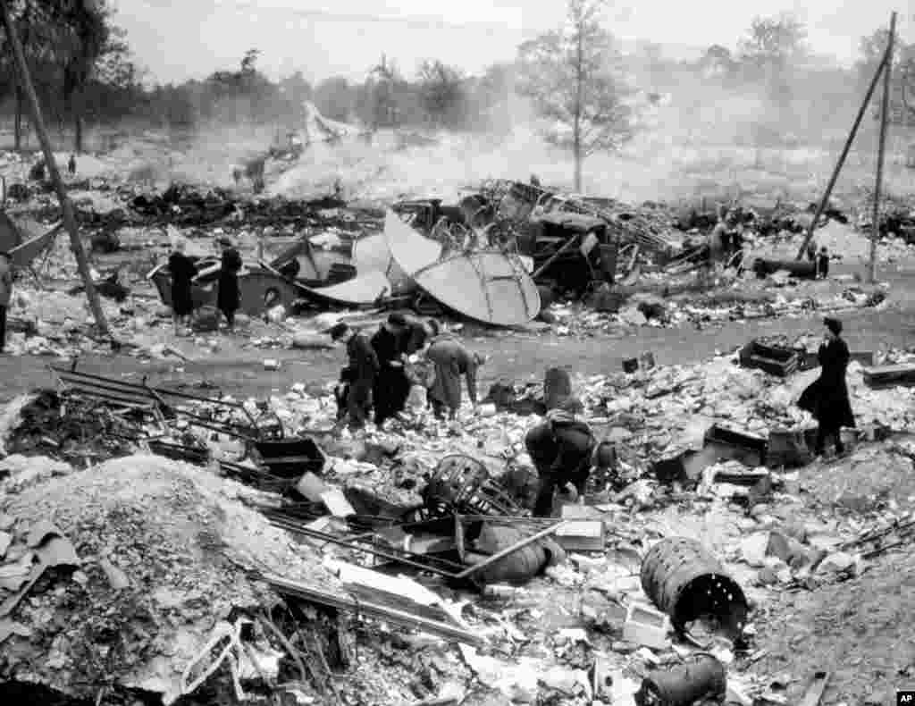 "People forage for food and fuel for cooking fires in a dumping ground near a Berlin airport. The foragers were known as ""hamsters,"" a name coined in 1918 -- the last time Germany was devastated by war."