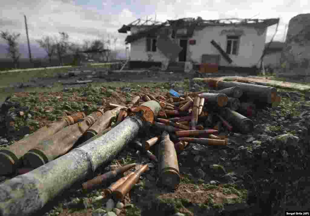 Unexploded ammunition is scattered around a damaged ammunition store near Aeygestan, on the outskirts of Stepanakert, the main city of the breakaway Azerbaijani region of Nagorno-Karabakh. (AP/Sergei Grits)