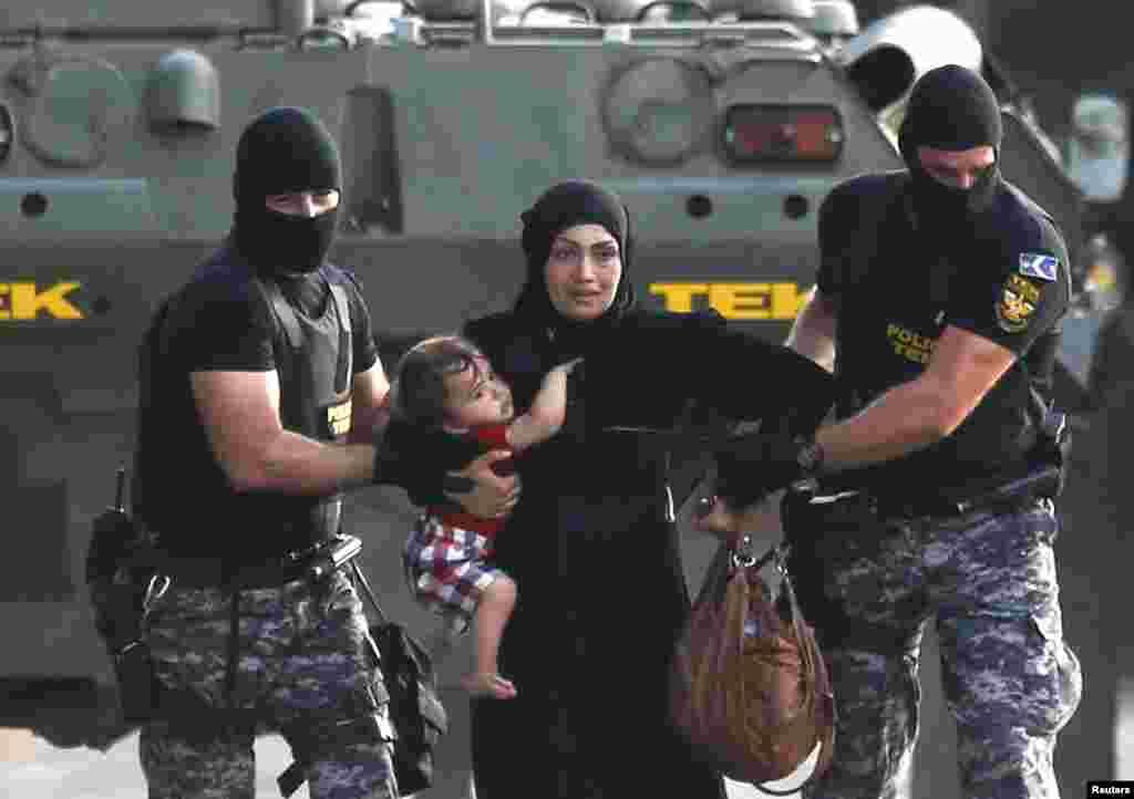 Венгерские полицейские ведут женщину-беженку с ребенком подальше от мест столкновений. 16 сентября
