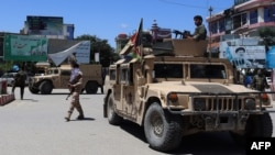 Afghan security forces sit in a Humvee vehicle amid ongoing fighting with Taliban militants in Kunduz in May.