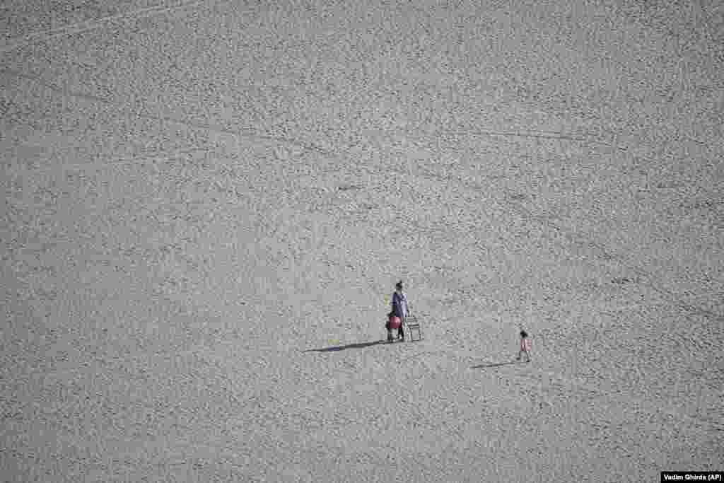Un copil merge după o femeie pe o plajă din portul Constanța.