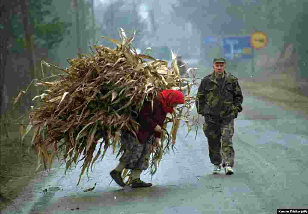 Bosanka nosi kukuruz, a pored nje prolazi vojnik u blizini nekadašnje prve linije u selu Lopare, u blizini Tuzle, 20. januar 1996. godine