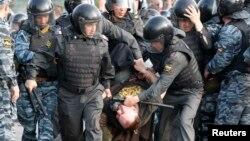 Орус полициясы нааразылыкка чыккан демонстранттарды кармап баратат, Москва, 6-май, 2012.