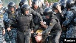 Полиция задерживает одного из участников акции протеста на Болотной площади в Москве. 6 мая 2012 года.