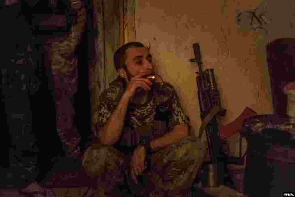 "Avram pauses for a cigarette during a a firefight that has lasted for more than an hour. When he first arrived in eastern Ukraine, he was in a 12-man unit with just four rifles between them. ""Some of us only had knives, some found grenades, and we just fought however we could."""