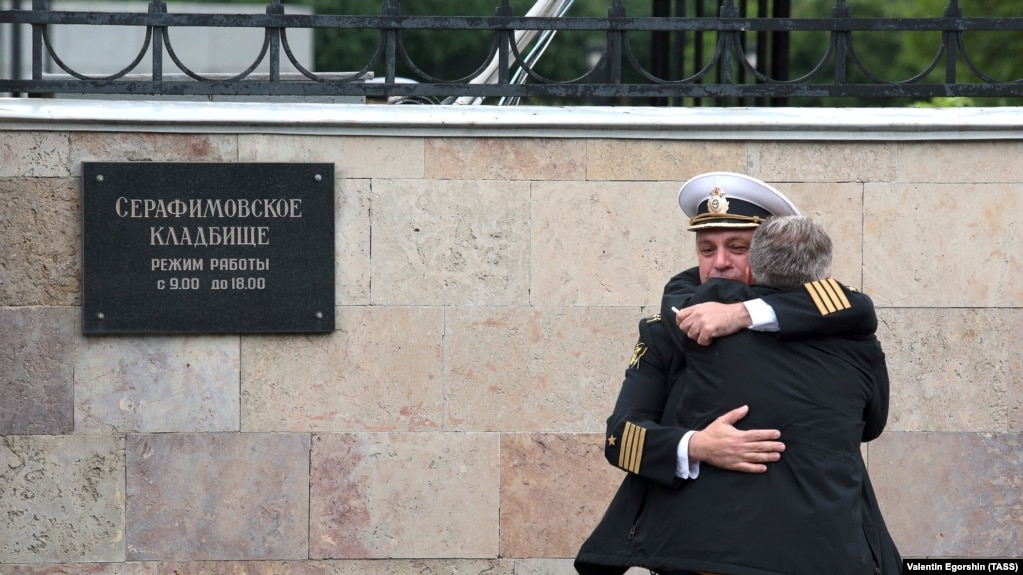 Russian Navy servicemen console each other ahead of a funeral service for 14 sailors who died in a submarine fire in the Barents Sea.