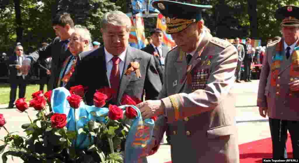 Аким города Алматы Ахметжан Есимов (слева) и генерал-армиии Сагадат Нурмагамбетов возлагают цветы к Вечному огню в Парке имени 28 гвардейцев-панфиловцев. Алматы, 9 мая 2013 года.