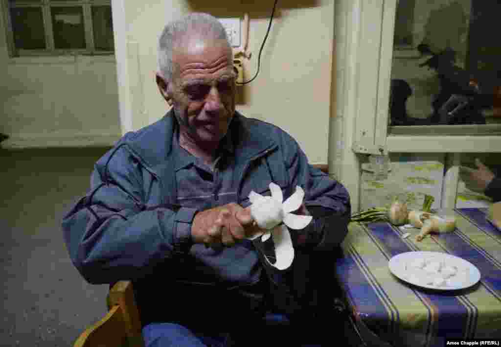 Retired builder Giorgos Kolaras peels a turnip at the doorway to the taverna.