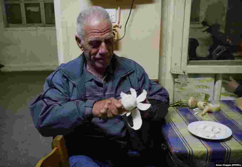 Пенсіонер Георгіос Коларас, колись муляр, чистить ріпу на порозі таверни