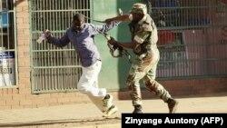 Zimbabweli esger bir protestçini urýar. 1-nji awgust, 2018 ý.