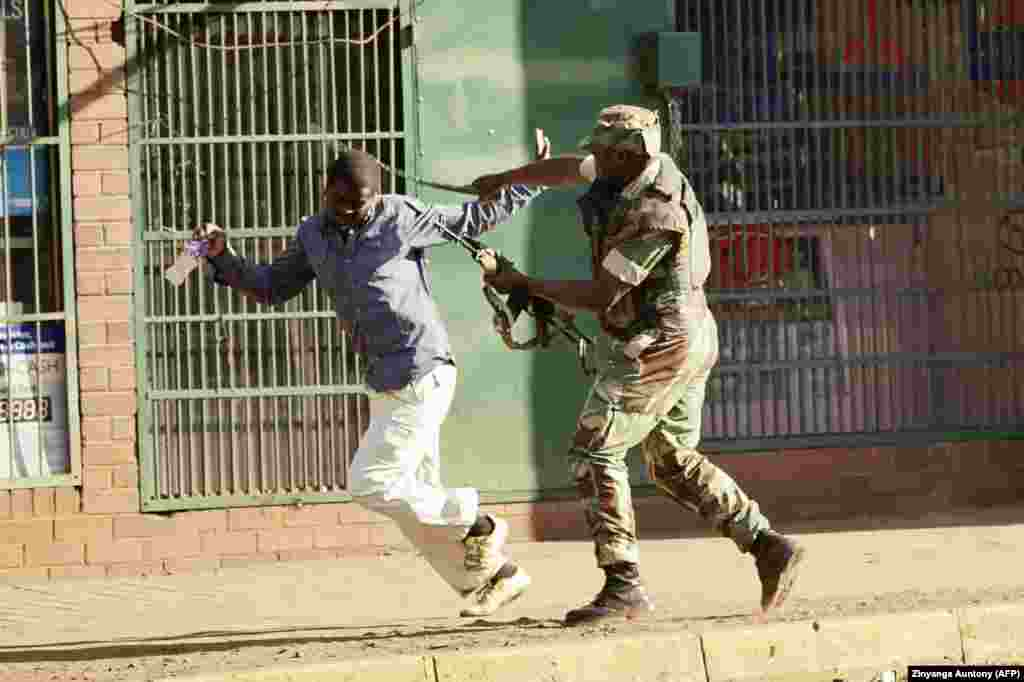 A Zimbabwean soldier beats a man in a Harare street as protests erupted over alleged fraud in the country's general election. (AFP/Zinyange Auntony)