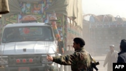Pakistani police guard trucks carrying NATO supplies crossing a street in Jamrud, Pakistan, earlier this month.