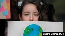 Девушка держит рисунок во время акции протеста против изменения климата в Бухаресте, Румыния, в пятницу, 20 сентября 2019 года.