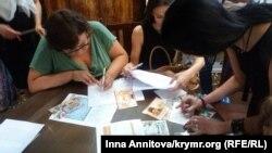 Пришедшие на мероприятие подписывают открытки политзаключенным