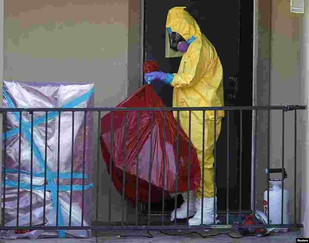 Саклану киеме кигән хезмәткәрләр Эбола белән авырган кеше яшәгән фатирны чистарта. Даллас, Техас штаты, АКШ. 6 октябрь 2014