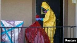 Работник в спецкостюме у квартирыв Далласе, где проживал Томас Дункан, у которого был диагностирован вирус Эбола. Техас, 6 октября 2014 года.