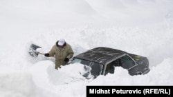 A man attempts to dig his car out of heavy snow in the Bosnia capital, Sarajevo.