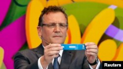 "FIFA Secretary-General Jerome Valcke holds the slip showing ""Russia"" during the draw for the 2014 World Cup in Sao Joao da Mata, Brazil, in December 2013."