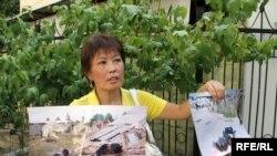 Ризада Жакыпбек принесла на суд фотографии разрушаемых властями домов. Алматы, 18 сентября 2008 года.