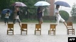 Студенттер су басқан жерден өтіп барады. Қытай, 18 маусым 2011 жыл. (Көрнекі сурет)