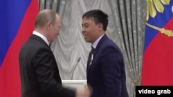 Rossiya prezidenti Vladimir Putin Kremlda Marat Isaevga medal topshirmoqda.