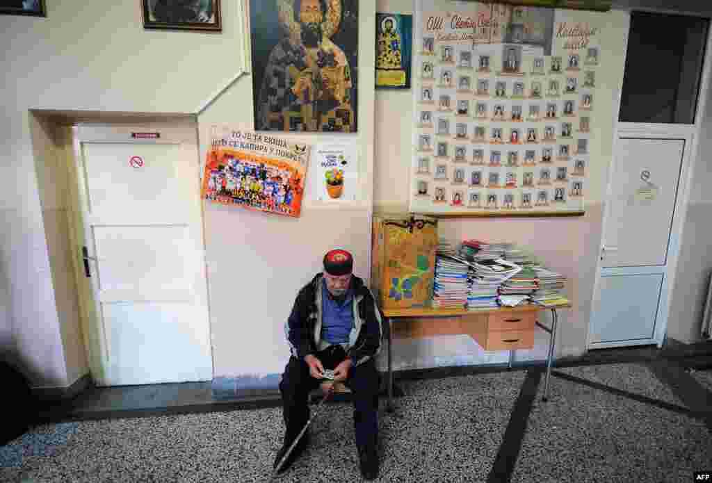 An ethnic Serb waits at a polling station in the ethnically divided city of Kosovska Mitrovica.