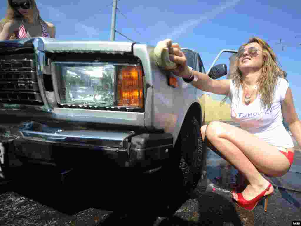Members of a social network group, who claim to be fans of Russian Prime Minister Vladimir Putin, stage a free outdoor car wash in Moscow in support of Russian carmakers on July 21.Photo by Alexandra Mudrats for ITAR-TASS