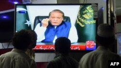 Pakistani men watch a televised address to the nation by Prime Minister Nawaz Sharif in Karachi on April 22.