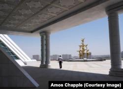 Мужчина выходит из-под тени под фрагментом сооружения монумента Конституции.