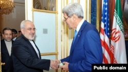 Iranian Foreign Minister Mohammad Javad Zarif (left) shakes hands with U.S. Secretary of State John Kerry at their meeting in Vienna on July 14.