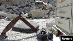 Противогаз лежит на земле посреди разрушений в результате авиаудара по базе террористической организации в Алеппо. 27 сентября 2014 года.