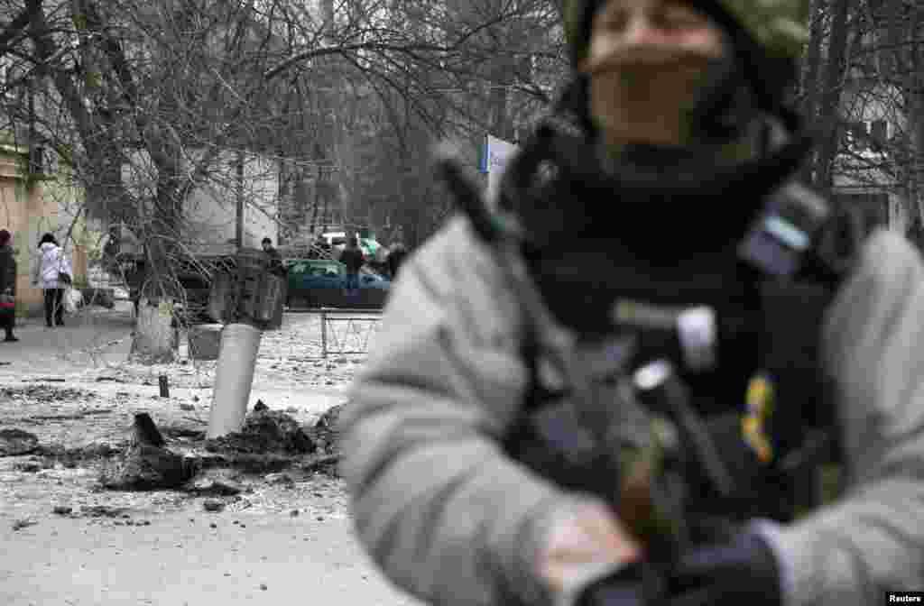 Украинский военный на месте, где упал один из снарядов.