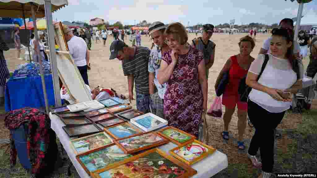 Відвідувачі розглядають роботи майстрів прикладного мистецтва і художників
