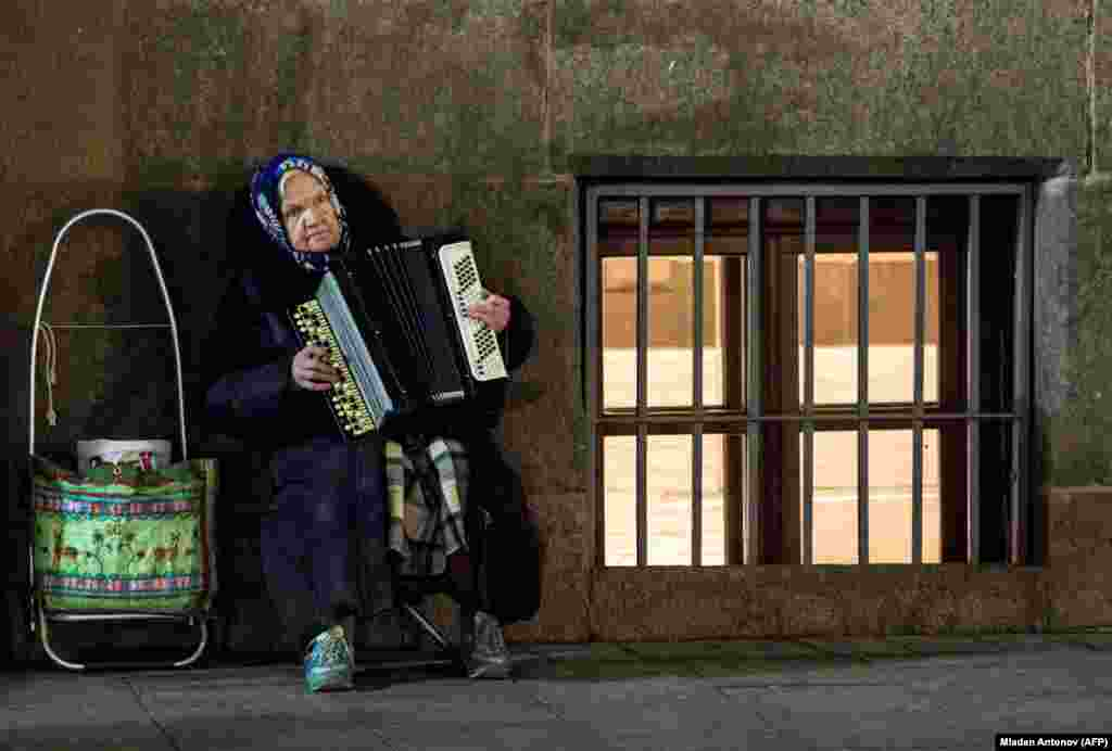 An elderly woman plays an accordion on the street in Moscow. (AFP/Mladen Antonov)