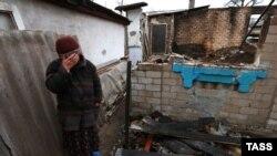 Женщина во дворе разбомбленного дома. Донецк, 14 декабря 2014 года.