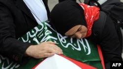 The wife of one of the nine activists killed in the Israeli raid on the Gaza aid convoy weeps on his coffin.