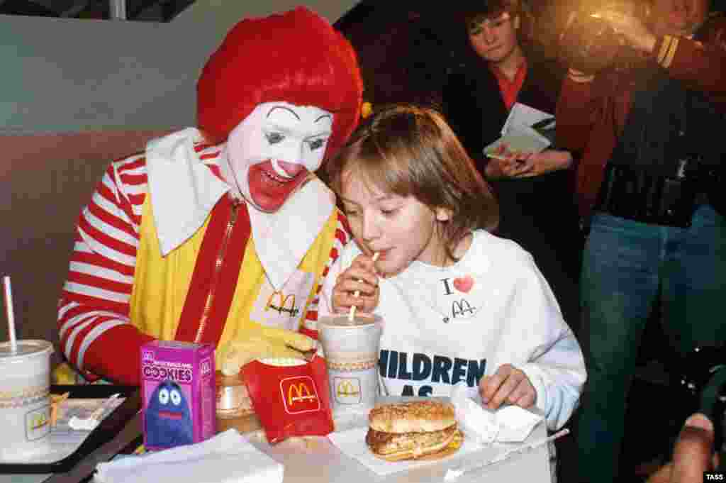 "Soviet schoolgirl and ""goodwill ambassador"" Katya Lycheva slurps some soft drink alongside a seemingly overeager ""Ronald McDonald"" in 1986."