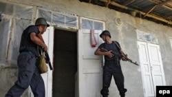 Police prepare to enter a home in an Uzbek district of Osh on June 22.