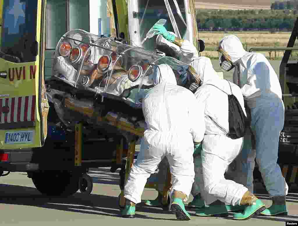 Дәрігерлер Либериядан Эбола дертін жұқтырып оралған деген күдікке ілінген адамды көлікке салып жатыр. Мадрид,Испания, 7 тамыз 2014 жыл.