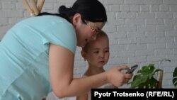 Мама Раяны Сауле показывает дочери фотографии. Алматы, 13 апреля 2018 года.