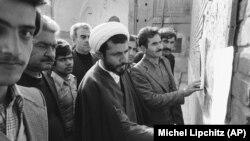მოლა მოქალაქეებთან ერთად კითხულობს გადასახლებული ისლამური ლიდერის, აიათოლა რუჰოლა ხომეინის ბოლო სიტყვებს თეირანის ბაზარში. 1978 წლის 16 დეკემბერი.